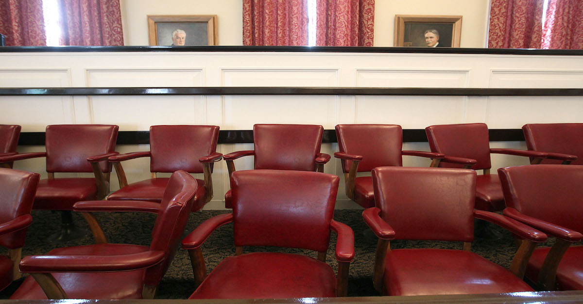 An image shows empty chairs from a jury box.