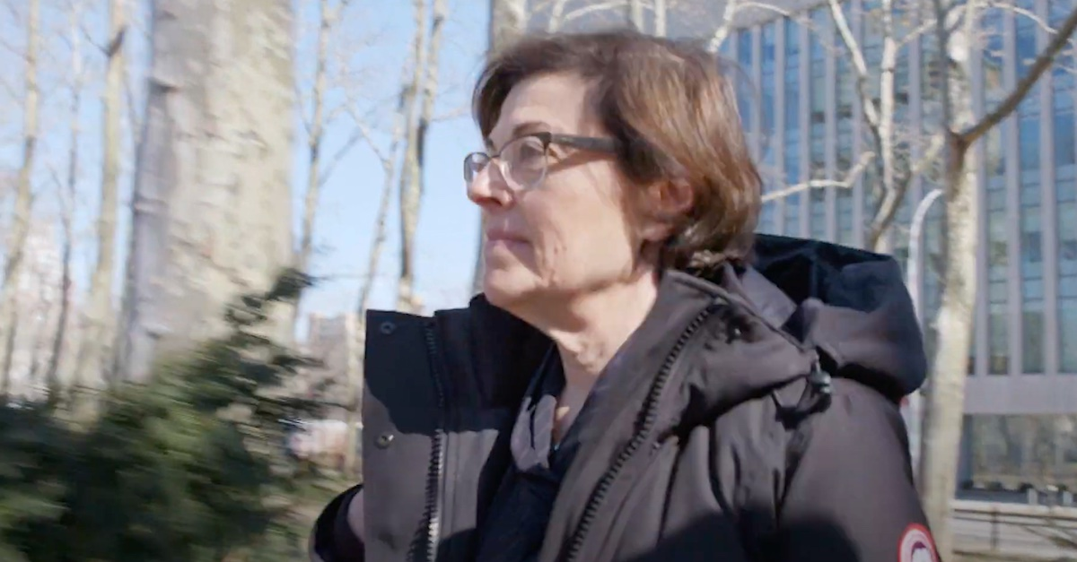 An image shows Nancy Salzman walking outside a courthouse.