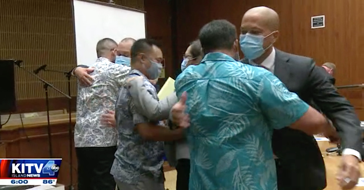 Geoffrey Thom, Christopher Fredeluces, and Zackary Ah Nee hugged their attorneys after a judge ruled that there was no probable cause to try them. (Image via KITV screengrab.)