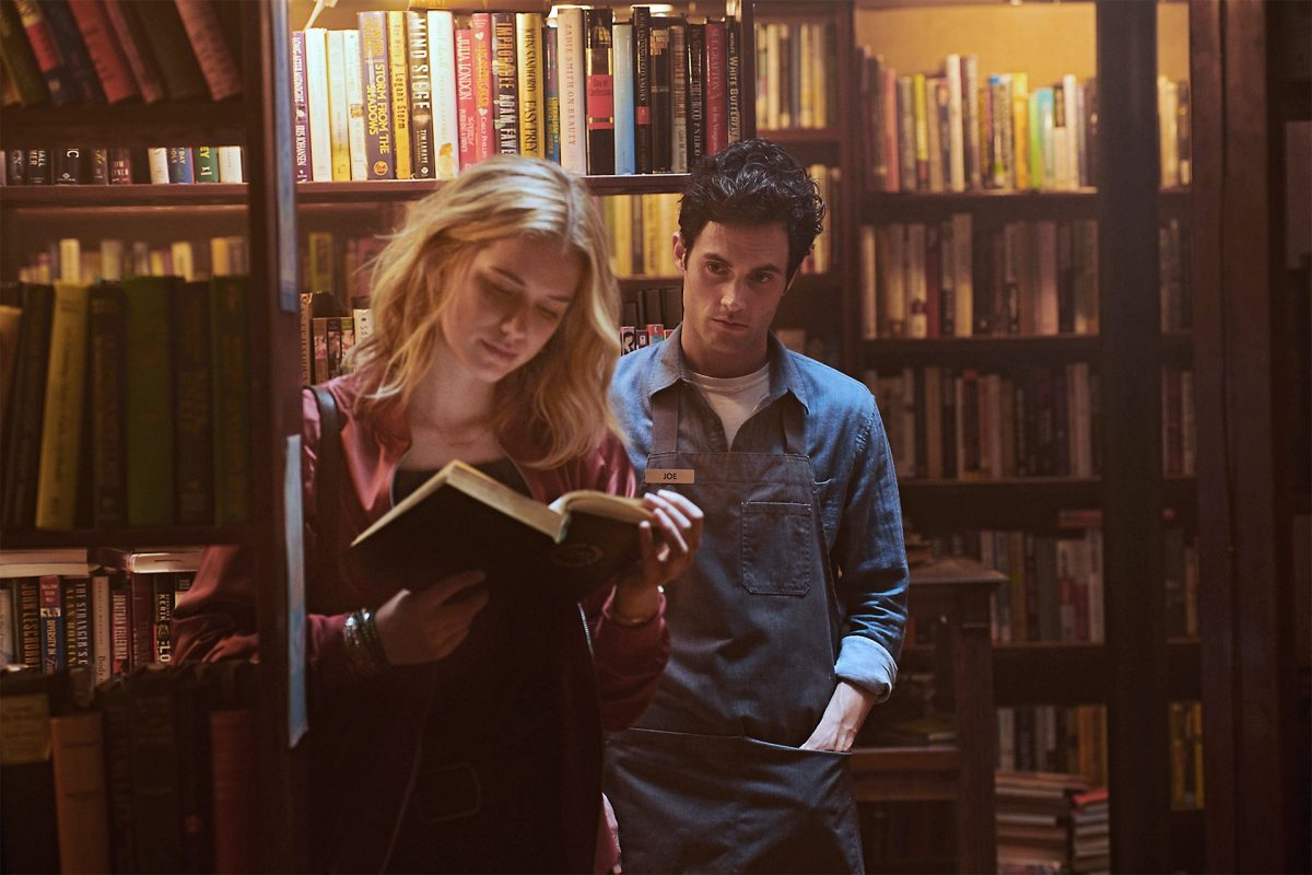 penn badgley as Joe looms behind and elizabeth lail as Beck in Netflix's You