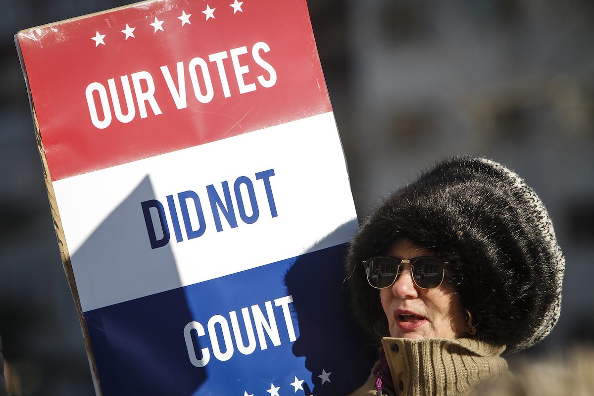 "Protestor holds a sign reading ""Our votes did not count."""