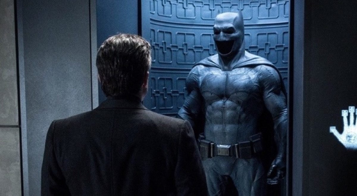Bruce Wayne looking at his Batman suit.