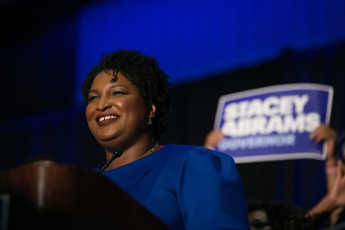 Stacey Abrams with campaign sign behind her