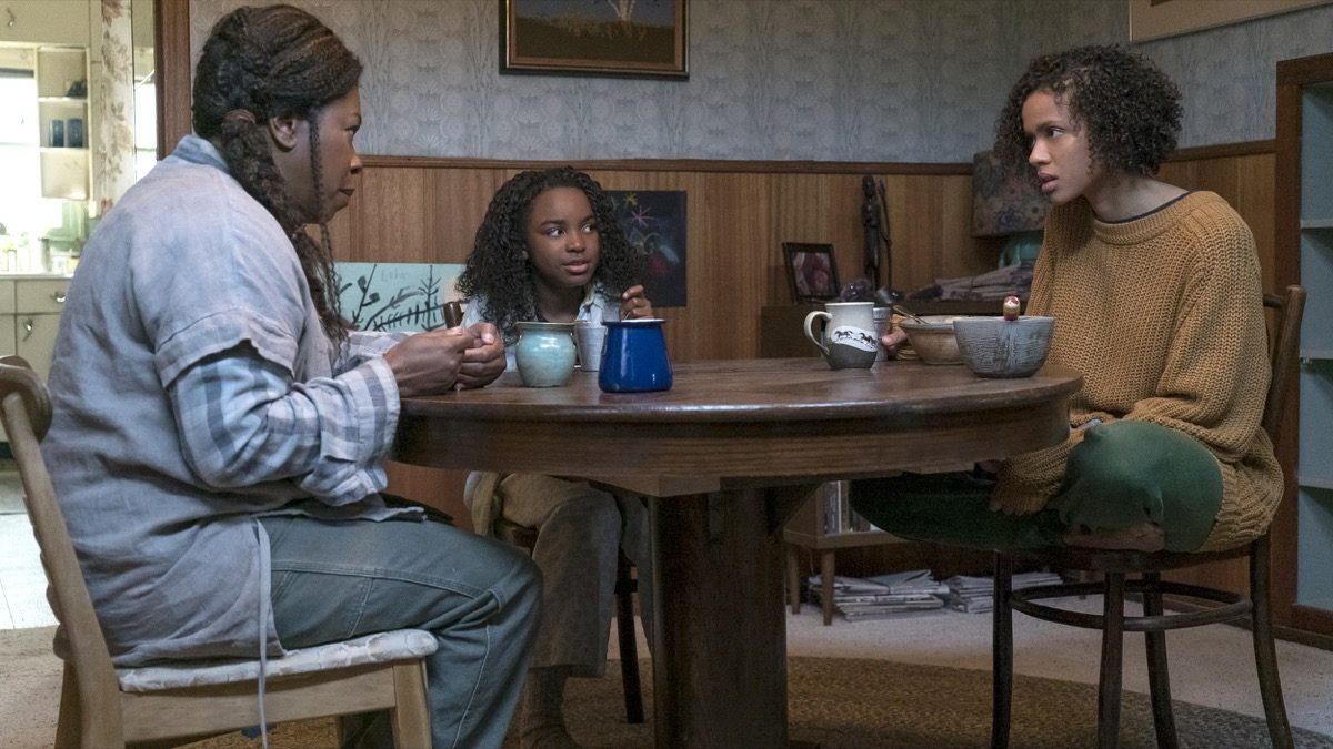 Fast color movie still the whole family sits around a table.