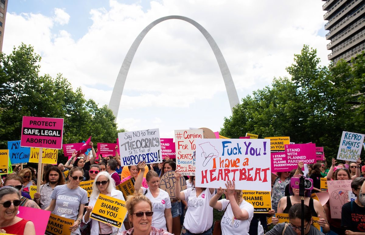 Protesters hold signs as they rally in support of Planned Parenthood in front of the St Louis arch.