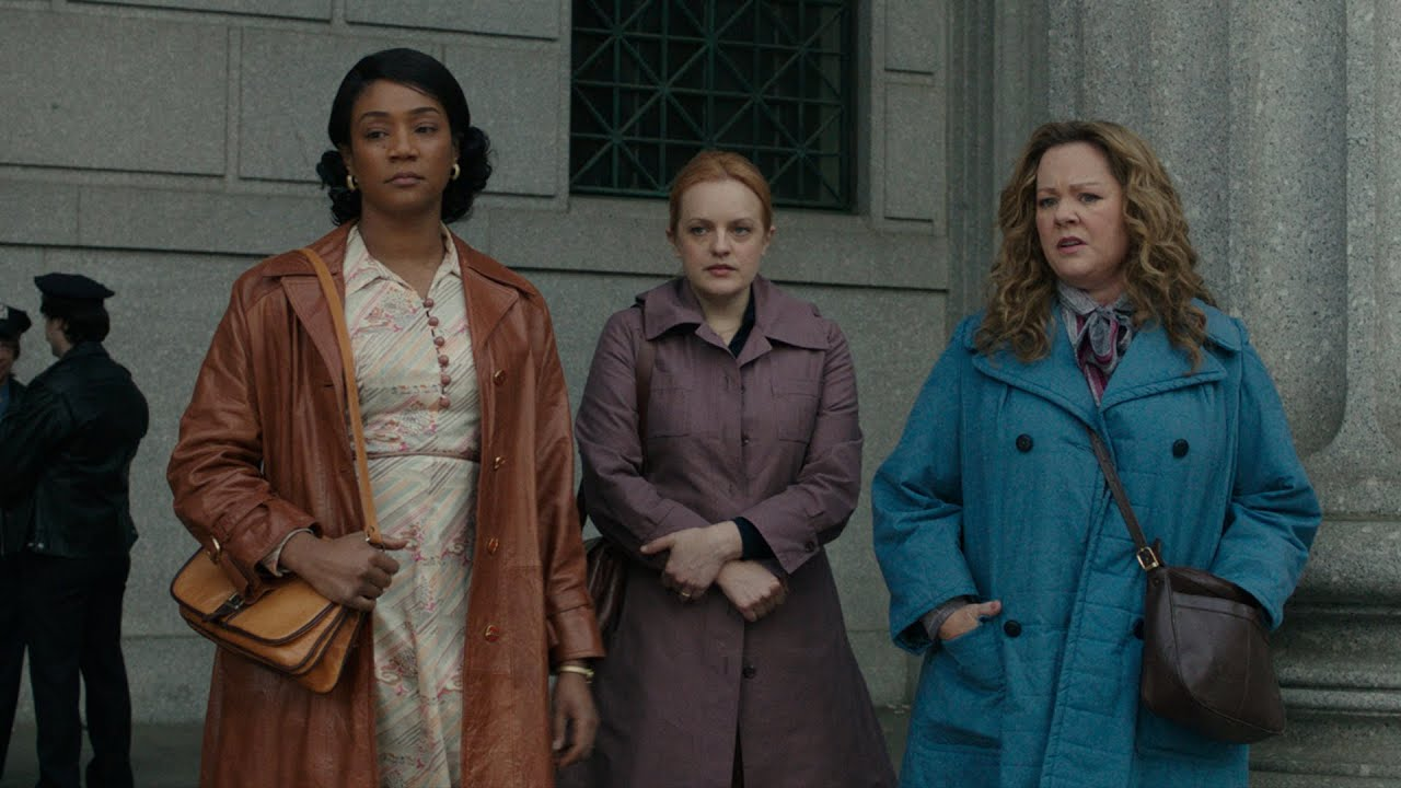 Tiffany Haddish, Elizabeth Moss, and Melissa McCarthy stand in 1970s period clothes.
