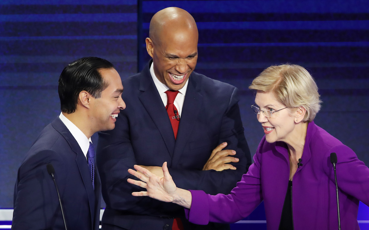 Julian Castro, Sen. Cory Booker (D-NJ) and Sen. Elizabeth Warren (D-MA) laugh together during the first night of the Democratic presidential debate