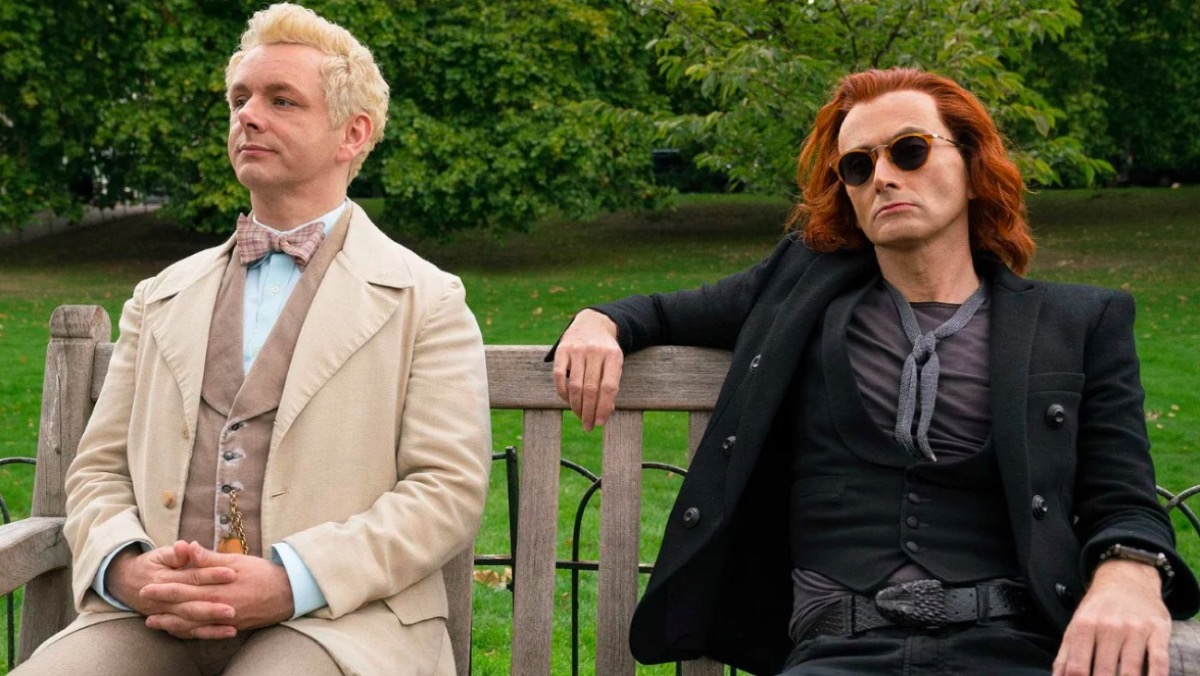 Aziraphale and Crowley sit on a bench, looking kind of bored in Amazon Prime's Good Omens.