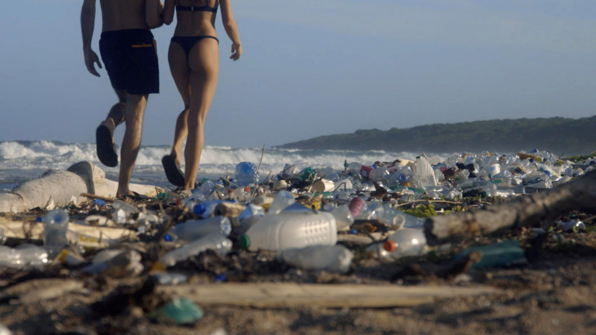 A man and woman walk on a beach covered in trash.