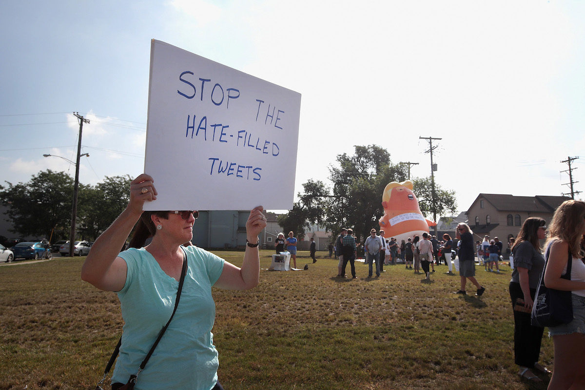 "An anti-Trump protester holds a sign reading ""stop the hate-filled tweets."""