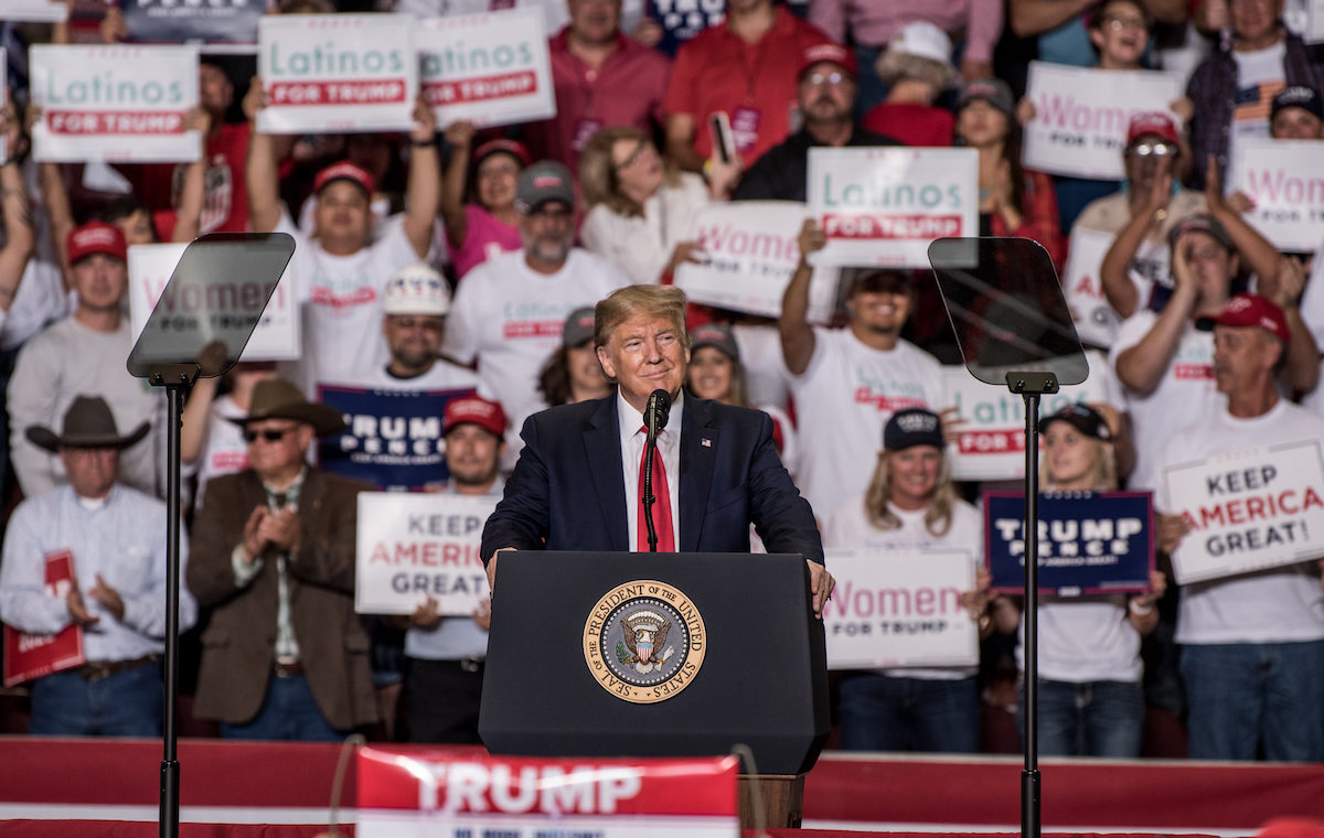 Donald J. Trump speaks at a rally with supporters holding Latinos for Trump signs behind him.