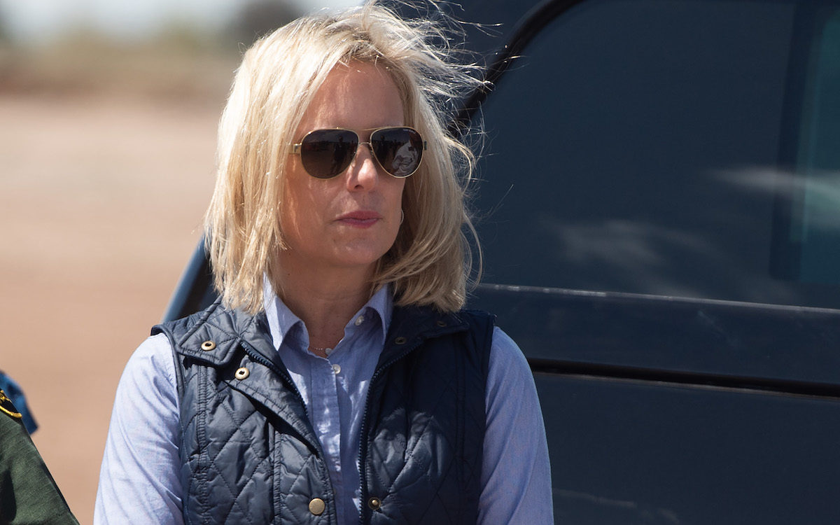 Secretary of Homeland Security Kirstjen Nielsen waits for US President Donald Trump as he arrives to tour the border wall.