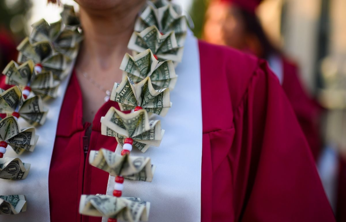 A graduating student wears a money lei, a necklace made of US dollar bills.