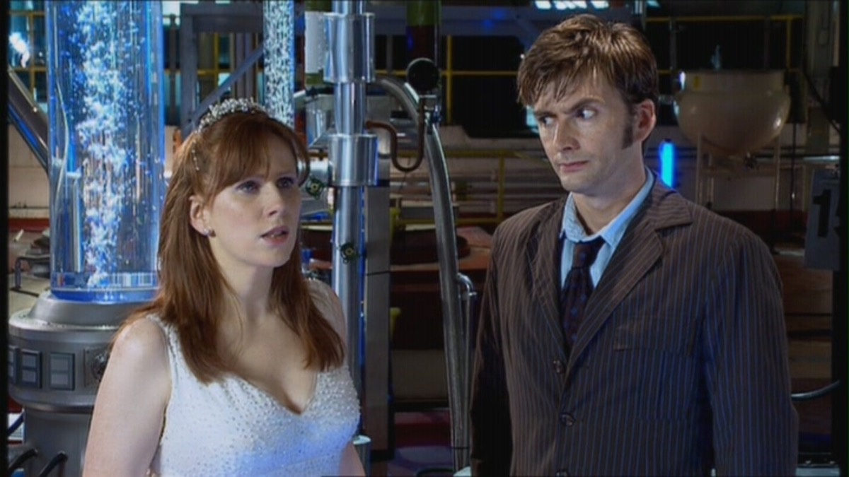 Donna Noble in a wedding dress as the Doctor raises an eyebrow at her.