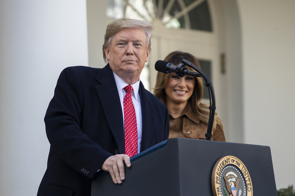 Donald Trump stands at a podium, in front of Melania, looking smugly at the camera.
