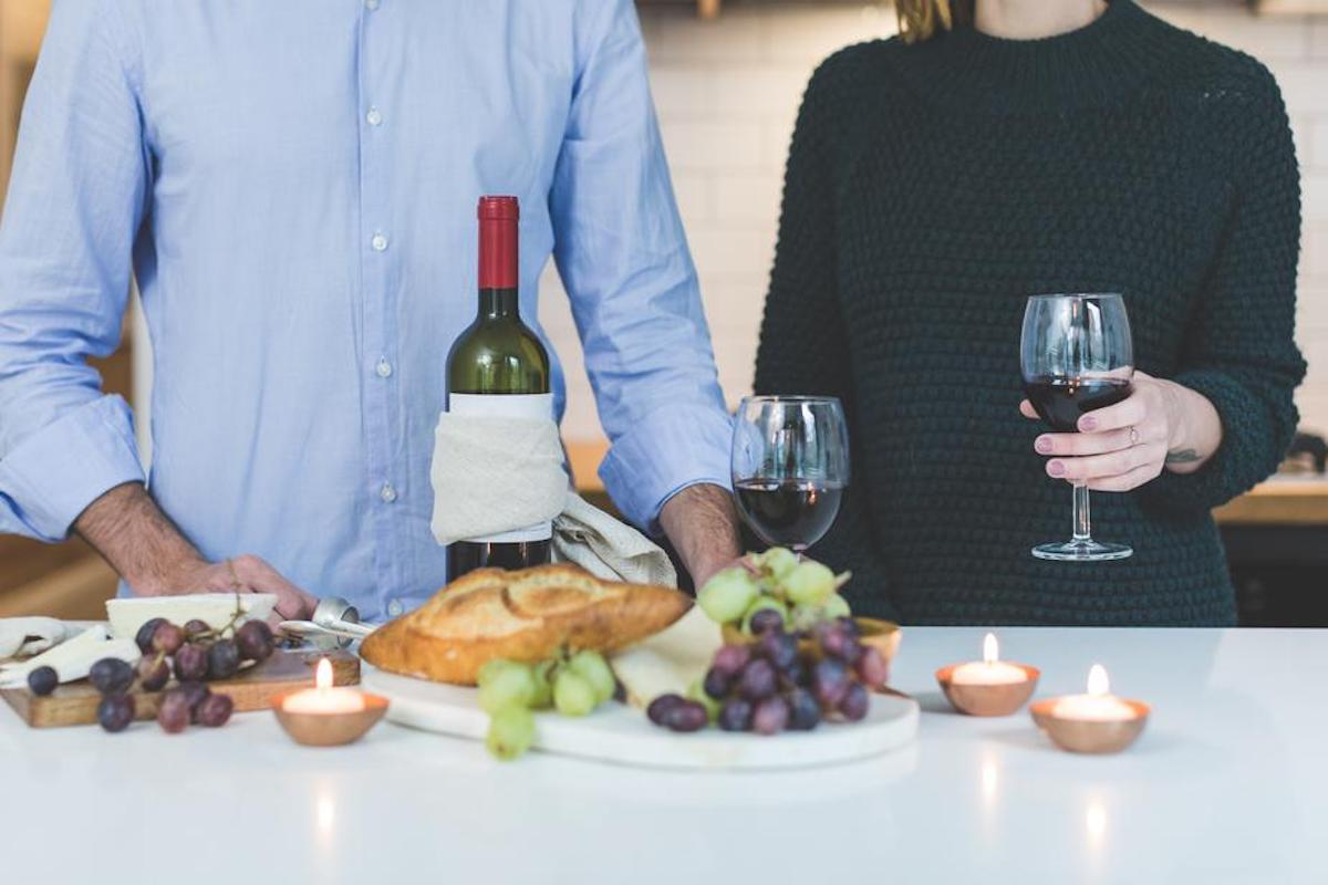 Heterosexual couple with wine and a cheese plate in front of them.