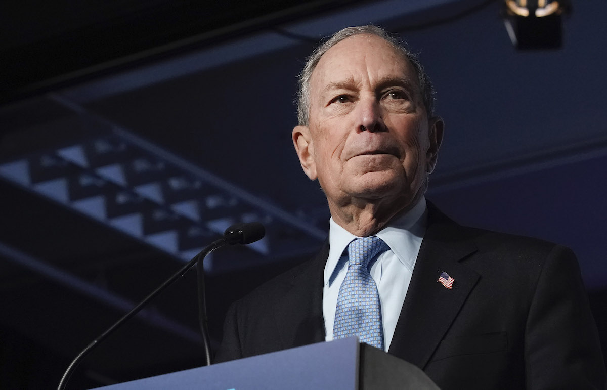 Mike Bloomberg stands at a podium.
