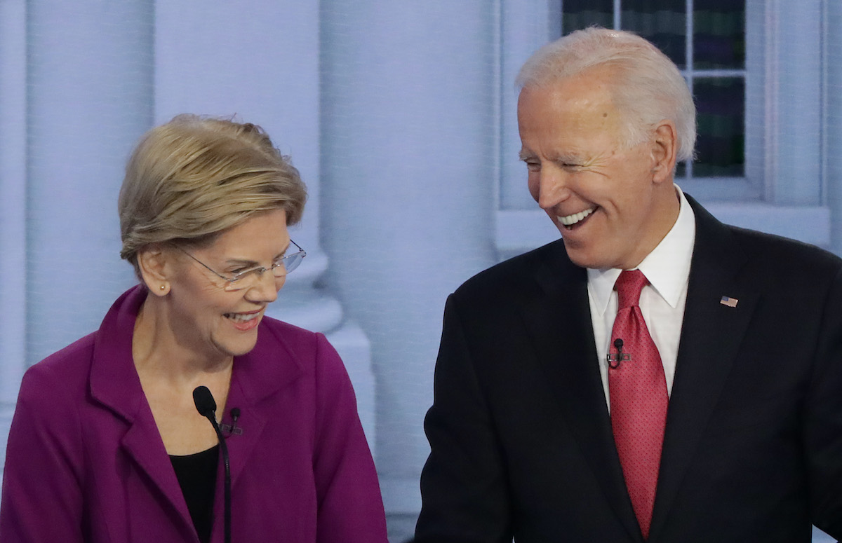 Elizabeth Warren and Joe Biden laugh during a debate.