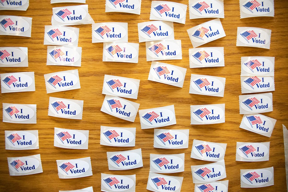 """""""I Voted"""" stickers cover a table at a polling station"""
