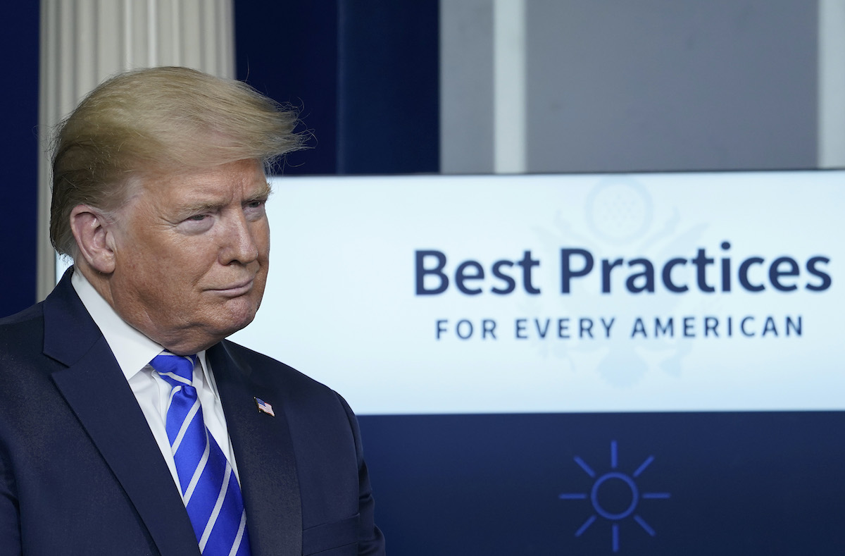 Donald Trump stands in front of a sign reading 'Best Practices for every American' during press briefing.