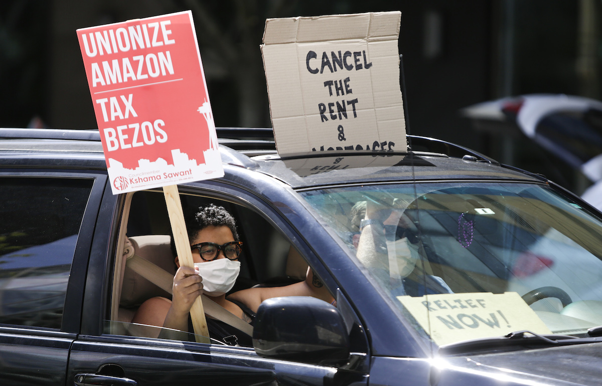 """People drive around the block with anti-Jeff Bezos signs as they participate in a """"car caravan"""" protest"""