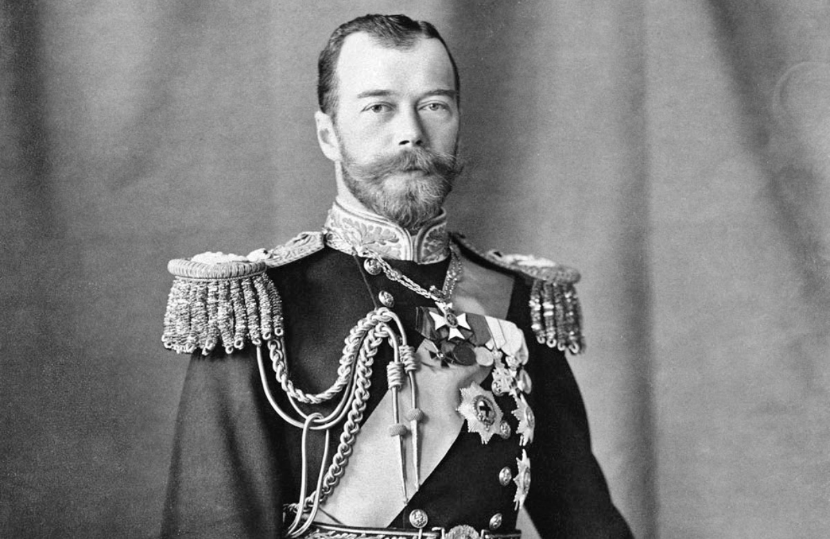 Gelatin silver print photograph of Nicholas II, Emperor of Russia. He is standing with his left hand resting on a bicorn hat on the decorative table beside him to the right. He is wearing an ornate naval uniform including epaulets, a sash and insignia. There is a pair of white gloves in his right hand and a sword by his side.
