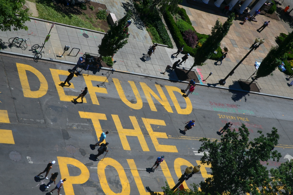 """Protestors Add """"Defund The Police"""" Messaging To Washington DC Street WASHINGTON, DC - JUNE 08: People walk down 16th street after """"Defund The Police"""" was painted on the street near the White House on June 08, 2020 in Washington, DC. After days of protests in DC over the death of George Floyd, DC Mayor Muriel Bowser has renamed that section of 16th street """"Black Lives Matter Plaza"""". (Photo by Tasos Katopodis/Getty Images)"""