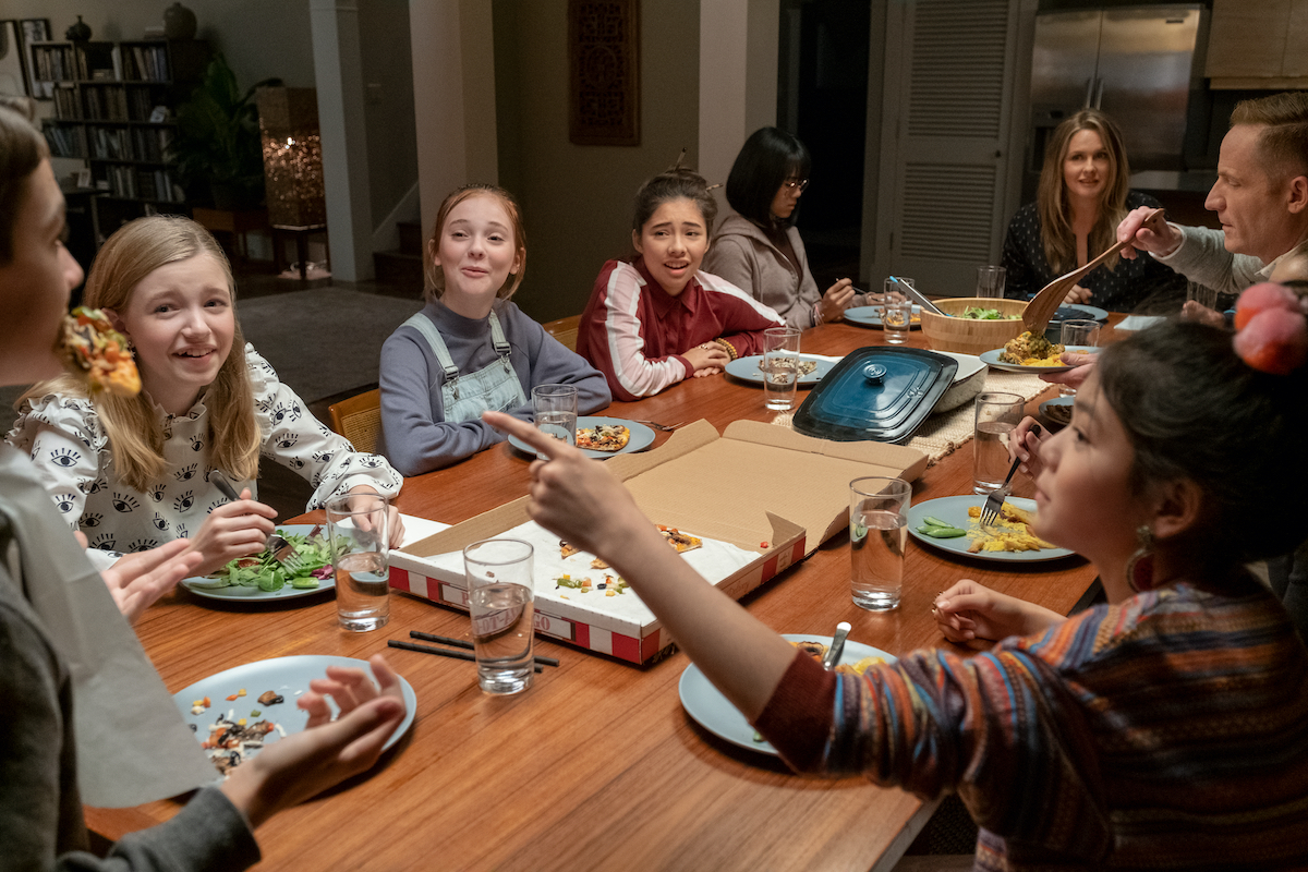 The cast of the Baby-Sitters Club gather around a dinner table.