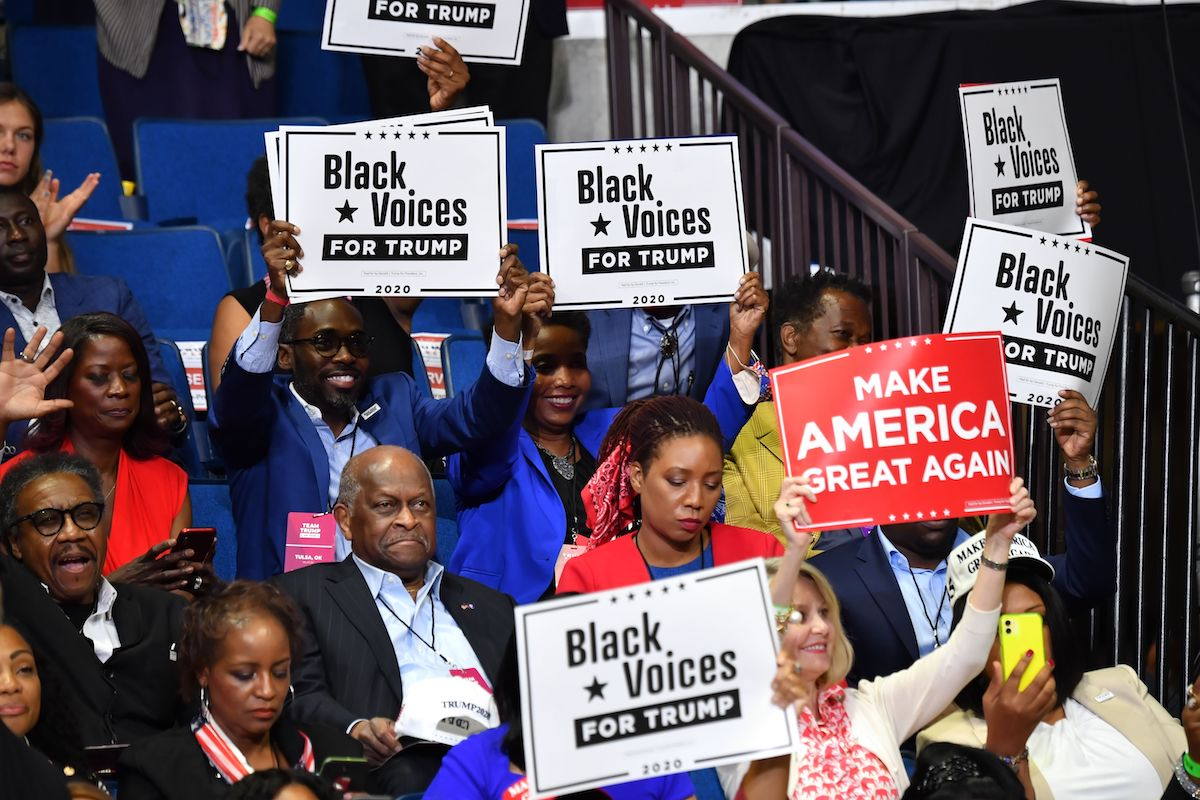 """Herman Cain and supporters of US President Donald Trump """"Black Voices"""" listen to him speak during a campaign rally"""