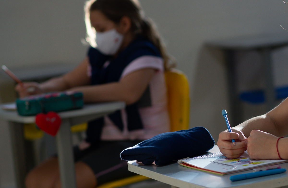 A young student wears a face mask while sitting at a school desk.