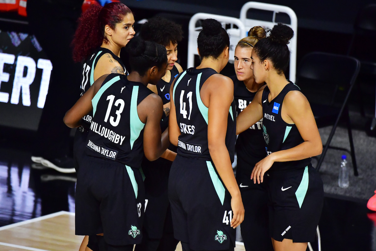 The New York Liberty starters huddle before a game, wearing jerseys bearing Breonna Taylor's name.