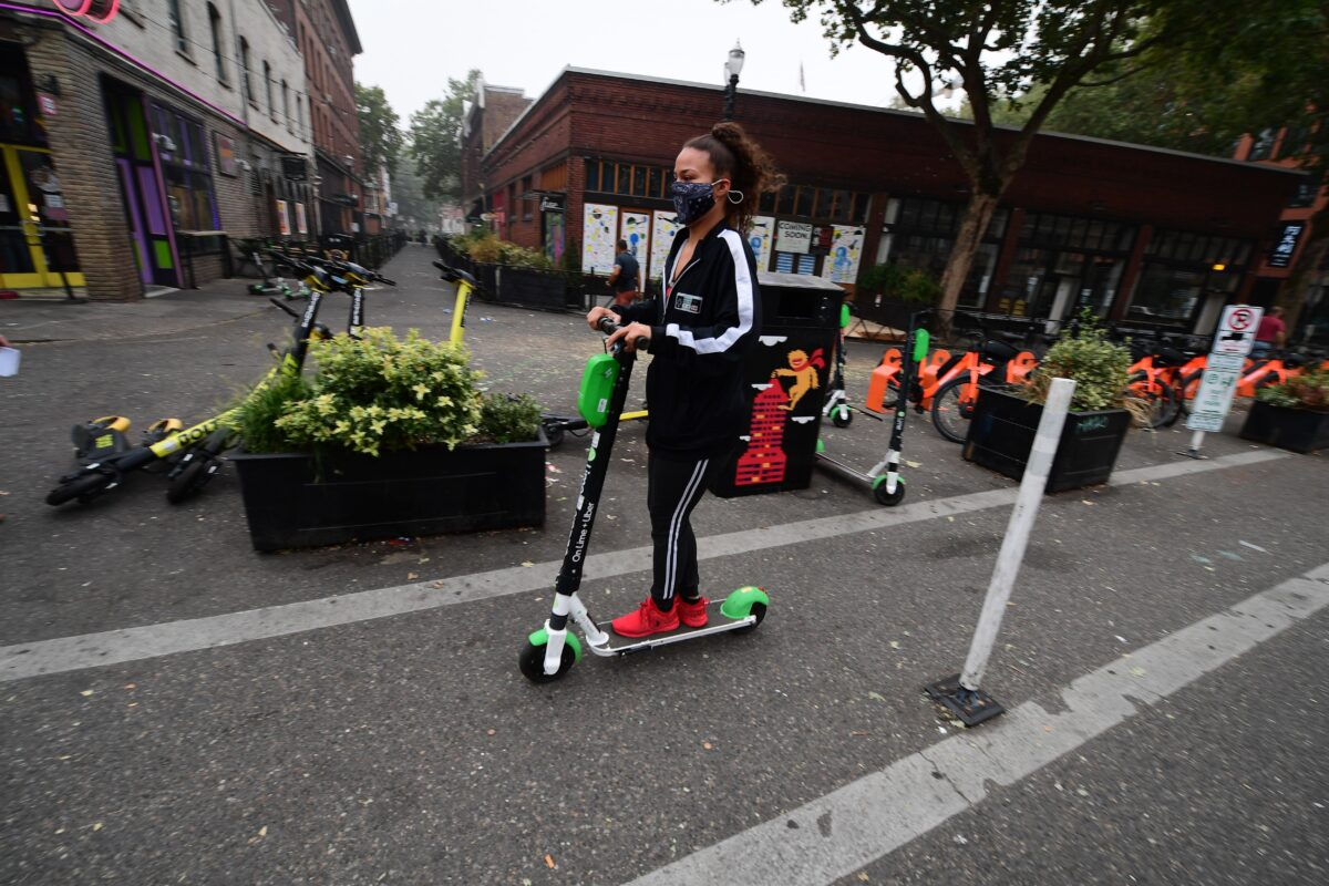 """Anarchy! A woman wears a mask as she rides a scooter in downtown Portland, Oregon where air quality due to smoke from wildfires was measured to be amongst the worst in the world, September 14, 2020. - The deadly fires spreading across three western US states are causing record-breaking pollution and a spate of health woes, from headaches and coughs to impaired vision, that have residents worried about the long-term consequences. Portland, the largest city in Oregon, has been blanketed for days by a dense smog that has sent pollution meters soaring. (Photo by Robyn Beck / AFP) / TO GO WITH AFP STORY BY CYRIL JULIEN """"As Oregon fires burn, smoggy air suffocates Portland residents"""" (Photo by ROBYN BECK/AFP via Getty Images)"""