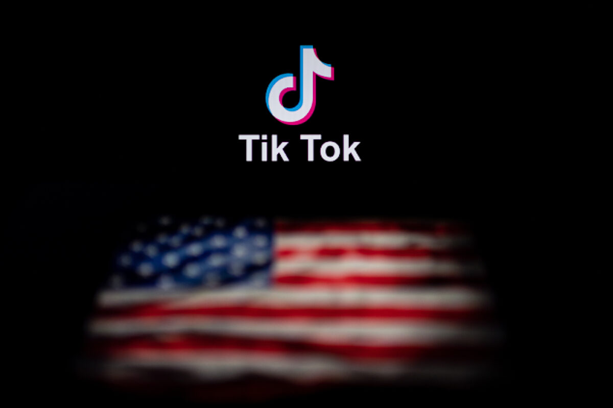 This photo illustration taken on September 14, 2020 shows the logo of the social network application TikTok (top) and a US flag (bottom) shown on the screens of two laptops in Beijing. - US tech giant Microsoft said on September 13 its offer to buy TikTok was rejected, leaving Oracle as the sole remaining bidder ahead of the imminent deadline for the Chinese-owned video app to sell or shut down its US operations. (Photo by NICOLAS ASFOURI / AFP) (Photo by NICOLAS ASFOURI/AFP via Getty Images)