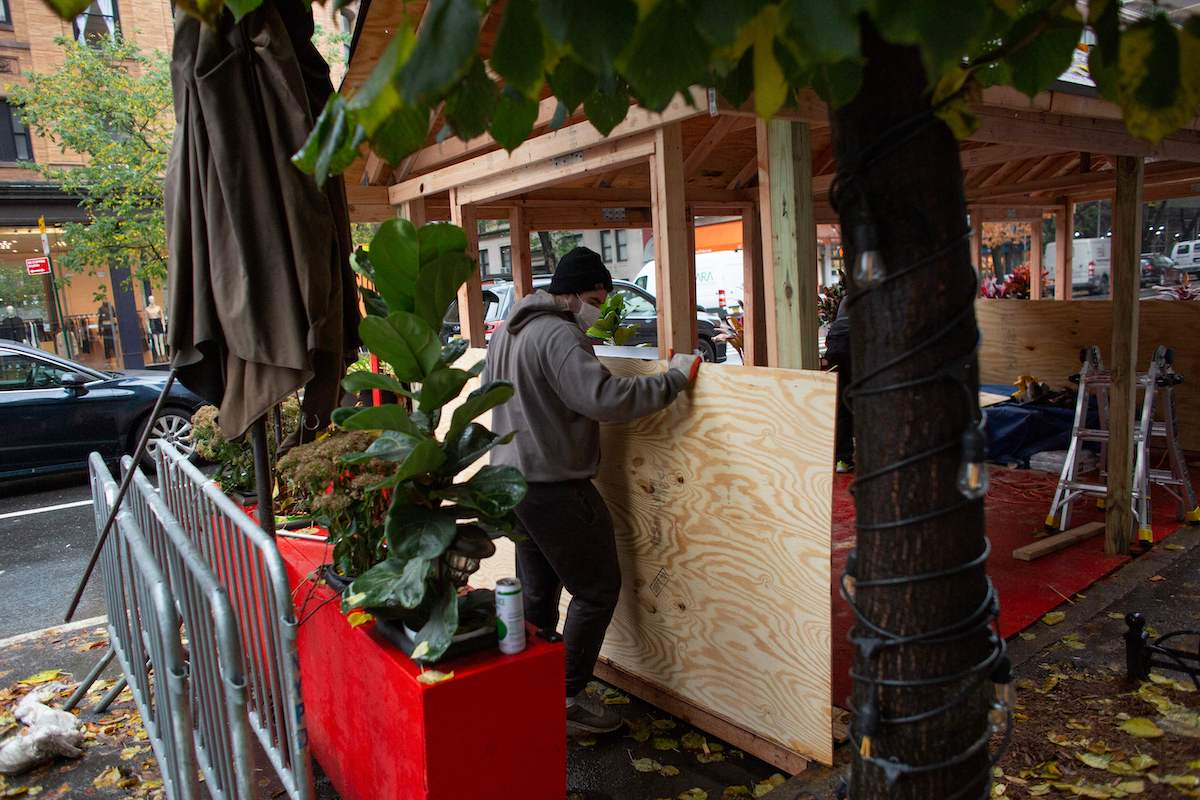 Workers build up a outdoor area outside a restaurant in New York