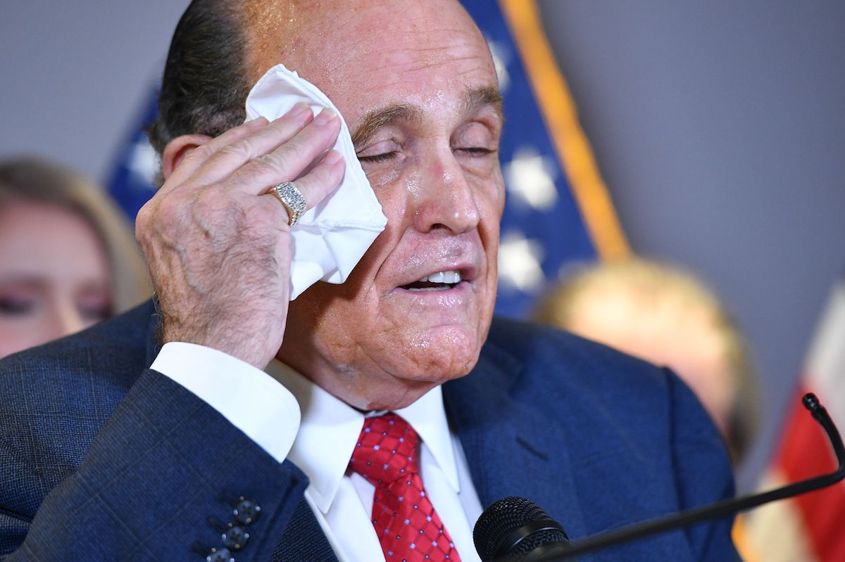 Rudy Giuliani wipes his sweaty face with a handkerchief during a press conference.