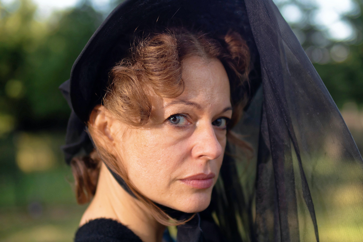Suzan Anbeh as Gesche Gottfried in Effigy stares at the camera while dressed in an elaborate mourning hat.