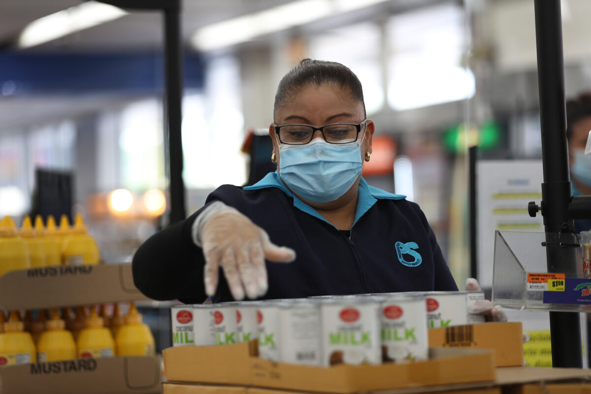 MIAMI, FLORIDA - APRIL 13: Lorena Martinez wears a mask and gloves as she works as a cashier at the Presidente Supermarket on April 13, 2020 in Miami, Florida. The employees at Presidente Supermarket, like the rest of America's grocery store workers, are on the front lines of the coronavirus pandemic, helping to keep the nation's residents fed. (Photo by Joe Raedle/Getty Images)