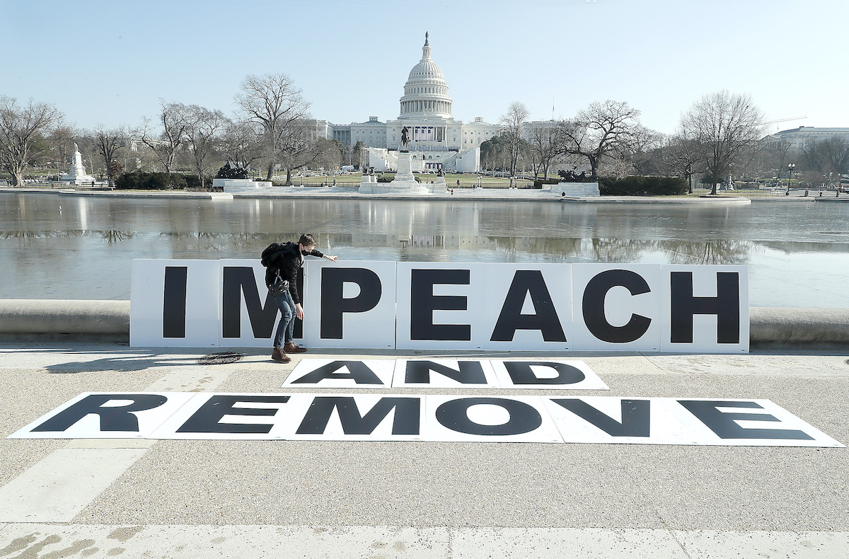 People gather at the base of the U.S. Capitol with large IMPEACH and REMOVE signs