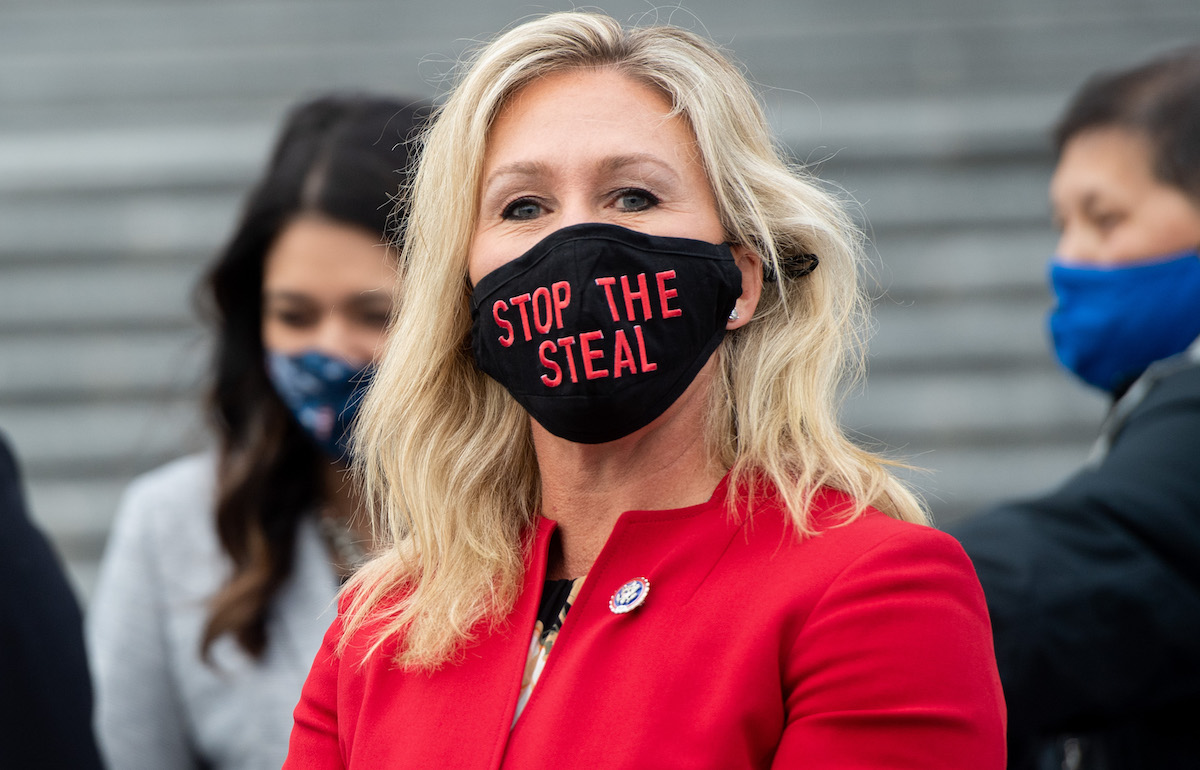 """Rep. Marjorie Taylor Greene looks at the camera while wearing a black mask reading """"Stop the Steal"""" in red letters."""