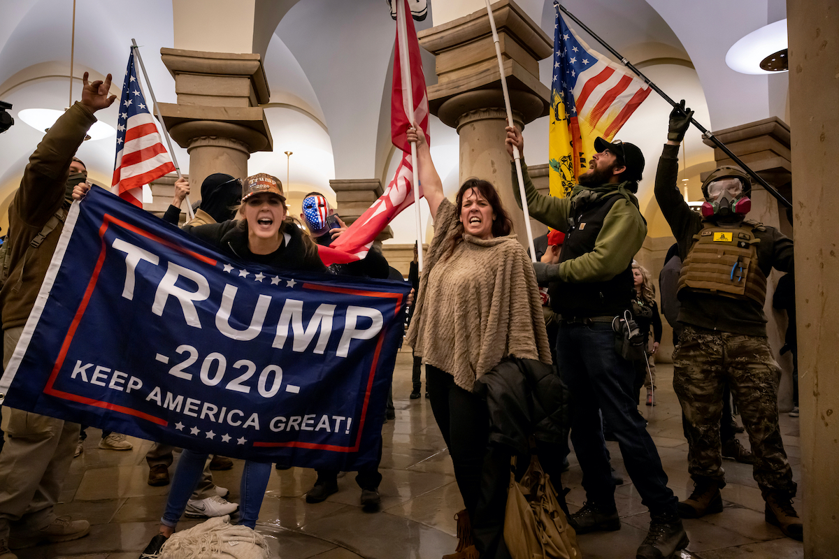 Trump supporters wave a Trump 2020 flag during the Capitol riot.