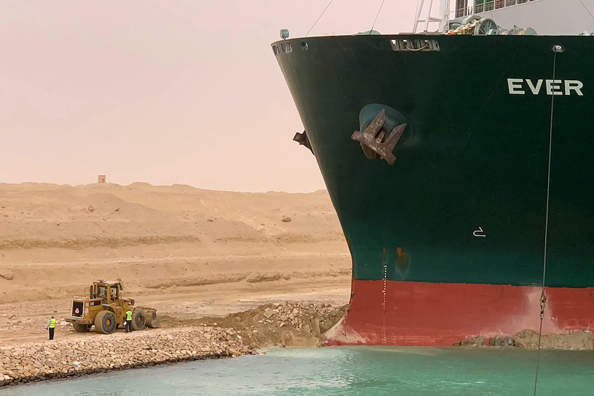 The stuck container ship Ever Given next to a tiny little digger working to get it out.