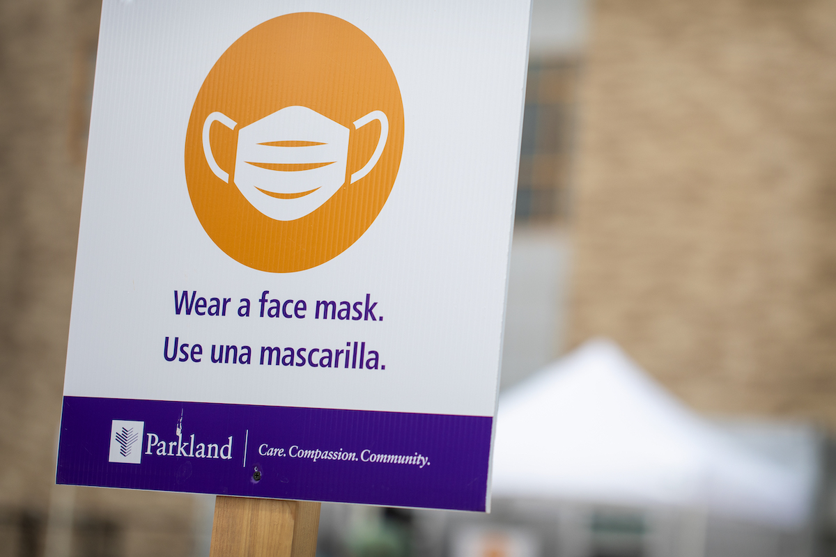 """A sign reading """"wear a mask"""" at a covid testing site."""