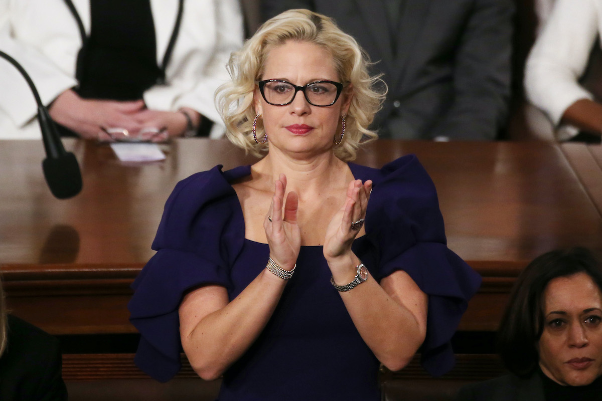 (image: Mario Tama/Getty Images) Sen. Krysten Sinema (D-AZ) applauds during the State of the Union