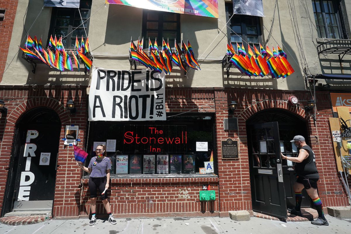 """The Stonewall Inn in New York flies LGBTQIA flags and a sign reading """"Pride is a riot #BLM"""""""