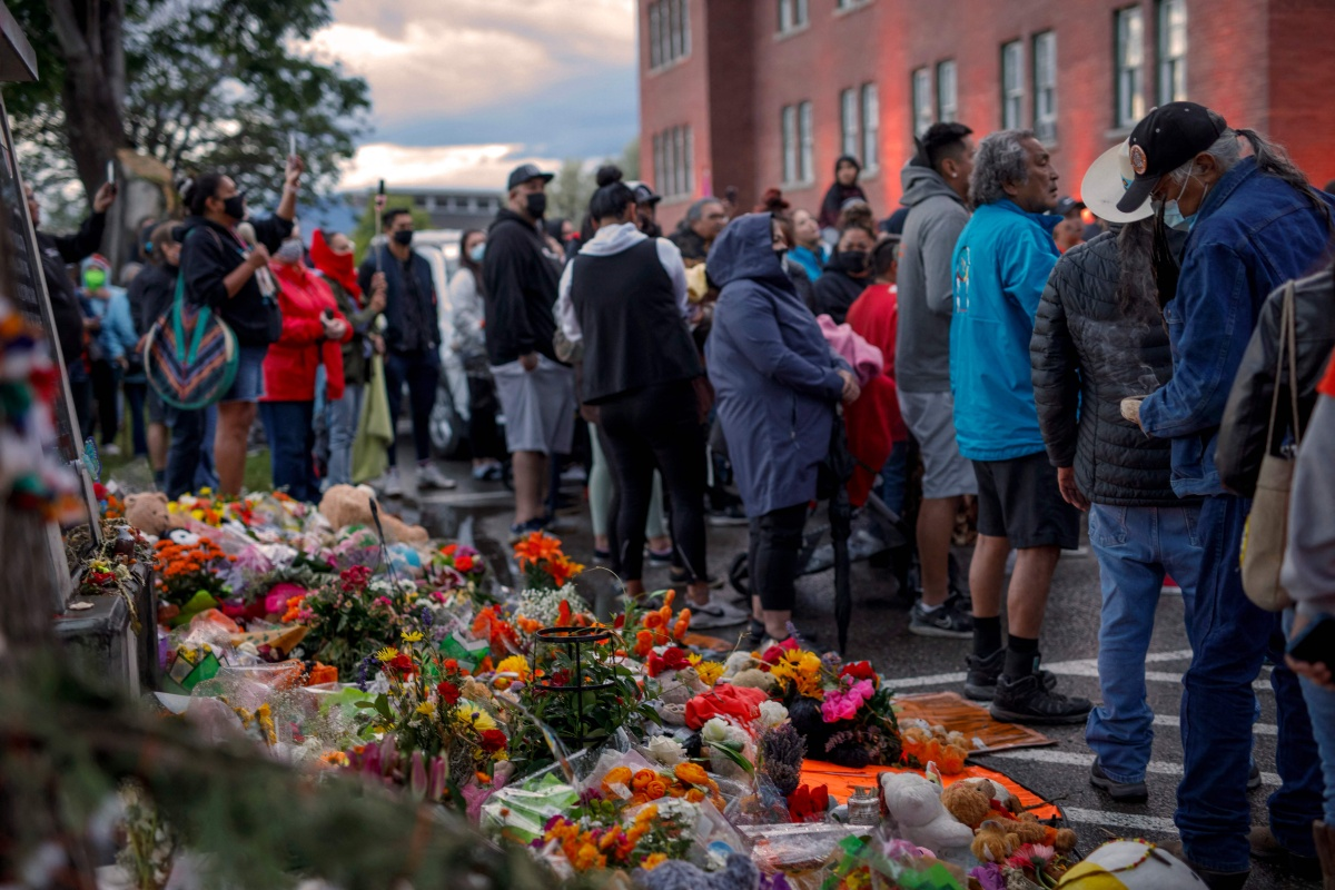 CANADA-INDIGENOUS-SCHOOL People gather outside the former Kamloops Indian Residential School as they welcome a group of runners from the Syilx Okanagan Nation taking part in The Spirit of Syilx Unity Run, following the discovery of the remains of 215 children buried near the facility, in Kamloops, British Columbia, Canada, on June 5, 2021. - The Spirit of Syilx Unity Run is an annual run to unify the community while addressing mental health and cultural rejuvenation. (Photo by Cole Burston / AFP) (Photo by COLE BURSTON/AFP via Getty Images)