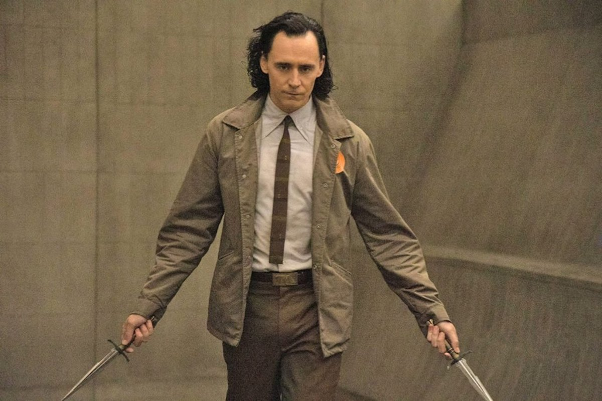 Tom Hiddleston as Loki is dressed in his TVA suit and holds two daggers
