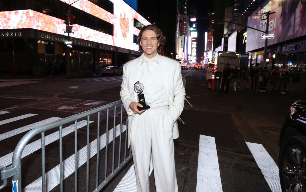 Aaron Tveit holding his Tony award outside on the streets of NYC