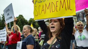 A gathering of anti-vaccine protesters hold signs and yell