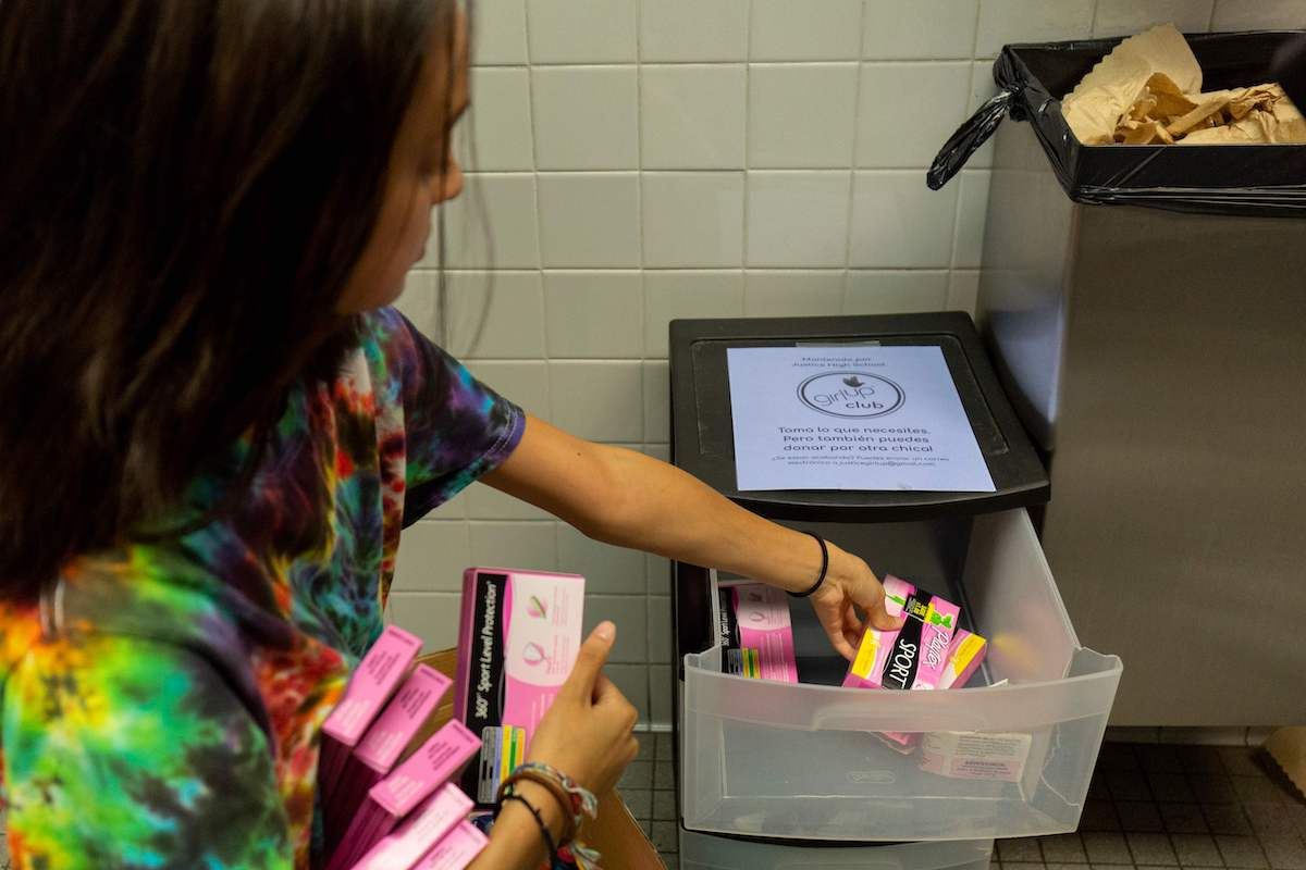 A student stocks a school bathroom with free pads and tampons